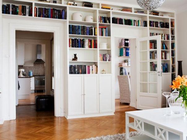 Книжный стеллаж на стене с дверью.