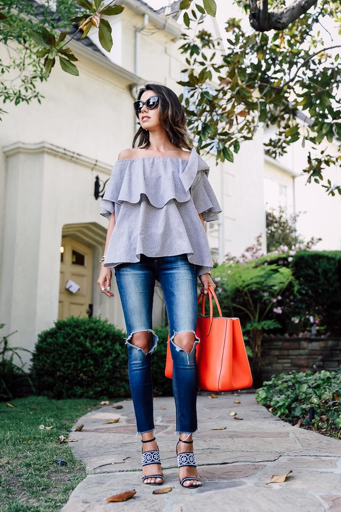 Блуза с открытыми плечами и драные джинсы: расслабенный образ для прогулки